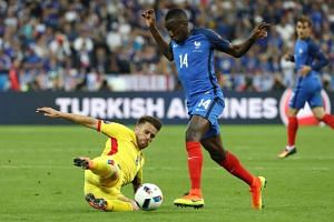 Romanian midfielder Mihai Pintilii (left) vying for the ball with French midfielder Blaise Matuidi.
