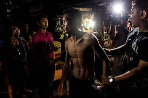 A half naked man is detained by policemen for violating drinking in public place in this picture taken on June 8.