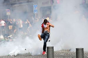 An England fan kicks away a tear gas canister after tear gas was released by French police in the city of Marseille, southern France, on June 11, 2016.