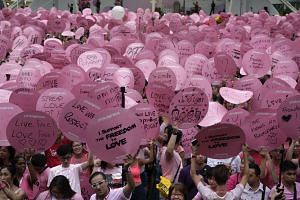 Participants holding up placards with their messages of love and support during the 8th edition of Pink Dot, on June 4, 2016.