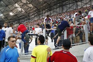 England fans climb over a fence to escape trouble in the stadium after the game on June 11, 2016.