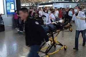 A bomb disposal expert checking a bag near the site of the attack. The incident took place near a check-in counter of Terminal Two at the Pudong International Airport. Medical attendants wheeling away a person on a gurney. Video clips online showed d