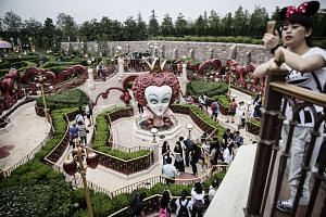 Visitors walk through the Alice in Wonderland Maze at Walt Disney Co.'s Shanghai Disneyland theme park on June 8, 2016.