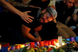 A man sits and cries after taking part in a candlelight memorial service the day after a mass shooting at the Pulse gay nightclub in Orlando, Florida, on June 13, 2016.