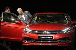 Prime Minister Najib Razak preparing to take the driver's seat in a new fourth-generation Proton Perdana sedan yesterday, during the launch of the Malaysian car manufacturer's latest vehicle.