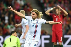 Iceland's midfielder Birkir Bjarnason celebrates the team's first goal during the Euro 2016 group F football match between Portugal and Iceland.