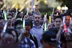 People hold electric candles during a memorial event for the victims of the Orlando mass shooting at Hong Lim Park.