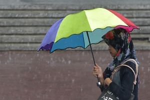 A woman walking in the rain in Jakarta on May 17.