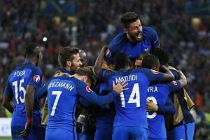 France's Olivier Giroud celebrates with team mates after Dimitri Payet scored their second goal.