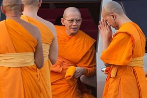 Abbot Phra Dhammachayo (center) arrives for a ceremony at the Wat Phra Dhammakaya temple in Pathum Thani province, north of Bangkok on Makha Bucha Day, in 2015.