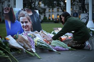 Floral tributes and candles are placed by a picture of slain Labour MP Jo Cox at a vigil in Parliament square in London on June 16.