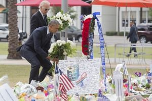 Mr Obama and Mr Biden laying flowers at a memorial at the Dr Phillips Centre for the Performing Arts in Orlando on Thursday for the victims of Sunday's mass shooting at the Pulse nightclub.