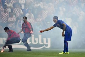 A flare is thrown onto the pitch by fans and is picked up by Croatia's Mario Mandzukic.
