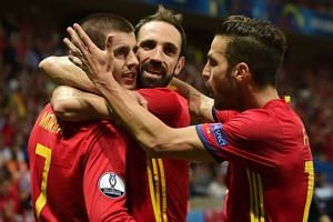 Spain's forward Alvaro Morata (L) celebrates with teammates after scoring.