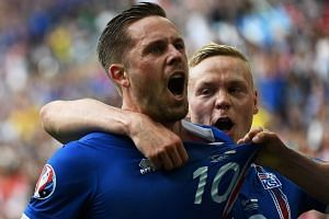 Iceland midfielder Gylfi Sigurdsson (left) celebrates after scoring his team's first goal.