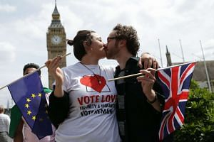 People pose kissing each other in a kiss chain holding EU and Union flags organised by pro-Europe 'remain' campaigners seeking to avoid a Brexit in the EU referendum in Parliament Square in front of the Houses of Parliament in central London on June