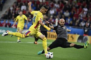 Romania's forward Florin Andone (left) vies for the ball with Albania's defender Arlind Ajeti during the Euro 2016  football match between Romania and Albania.