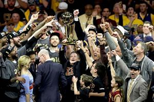 Cleveland Cavaliers owner Dan Gilbert, holds the Larry O'Brien Championship Trophy after the Cavaliers defeated the Golden State Warriors 93-89 in Game 7 of the 2016 NBA Finals.