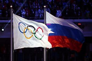 The Olympic flag (left) and the Russian flag during the closing ceremony of the Sochi 2014 Olympic Games.