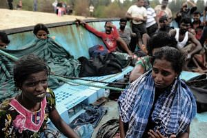 Migrants from Sri Lanka remain on their boat despite their vessel being washed ashore on the west coast of Lhoknga in Aceh Besar, on June 14, 2016.