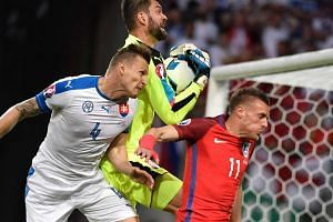 Slovakia goalkeeper Matus Kozacik (centre) grabs the ball next to Slovakia defender Jan Durica (left) and England forward Jamie Vardy.