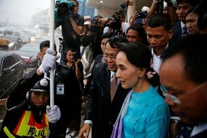 Aung San Suu Kyi leaves a meeting with migrant workers at the coastal fishery centre of Samut Sakhon, in Thailand, on June 23, 2016.