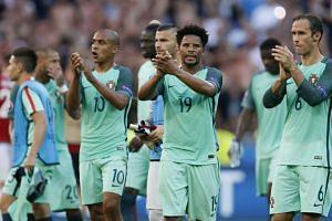 Portugal's Joao Mario, Eliseu and Ricardo Carvalho applaud their fans after the match.