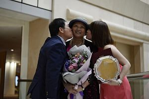 Cancer-stricken gymnastics coach Zhu Xiaoping (centre), with her husband Lin Zhenqiu and daughter Vanessa Lin, who is holding her special award for fortitude. She guided the Singapore team to a first-ever gold in last year's SEA Games group all-aroun