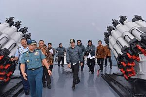 Indonesian President Joko Widodo (centre) on board the navy warship KRI Imam Bonjol yesterday, accompanied by several Cabinet ministers and other top officials. SEE TOP OF THE NEWS A4