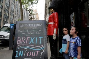 Children pose next to a chalkboard advertising a Brexit viewing event at The Churchill Tavern, a British theme bar.