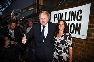 Former London Mayor Boris Johnson (centre) and wife Marina Wheeler (right) attend a polling station in North London on June 23, 2016.
