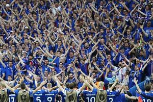 Iceland's players celebrate with their fans after their 2-1 win against Austria in Saint-Denis, France, on June 22.