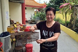 "Ms Sim holding a metal cage with cuttlefish bait used to trap rats. The situation has improved from three months ago, though temple staff and volunteers still see ""one or two small rats occasionally""."