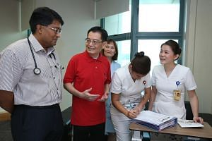 Mr Heng with Clinical Associate Professor John Abisheganaden from the Endoscopy Centre, Respiratory and Critical Care Medicine Clinic, and nurses of Tan Tock Seng Hospital yesterday. Six weeks after suffering a stroke, he is fit enough to go home.