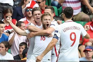 Poland midfielder Jakub Blaszczykowski (centre) celebrates scoring the opening goal with teammates.