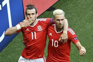 Wales' forward Gareth Bale (left) and midfielder Aaron Ramsey celebrate after McAuley's own goal.
