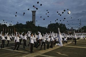 New officers celebrating at the end of yesterday's Officer Cadet Course commissioning parade at Safti Military Institute, which celebrates its 50th anniversary this year. At the parade, PM Lee paid tribute to the pioneer batch, saying that he hoped t