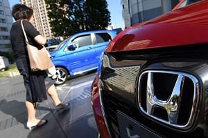A woman walks past vehicles by Japan's Honda Motor at the company's headquarters in Tokyo on May 13, 2016.