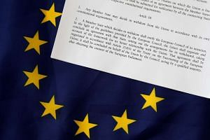 Article 50 of the EU's Lisbon Treaty that deals with the mechanism for departure is pictured with an EU flag in Brussels.