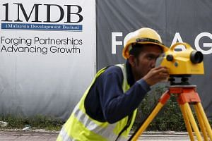 A construction worker works in front of a 1Malaysia Development Berhad (1MDB) billboard at the Tun Razak Exchange development in Kuala Lumpur, Malaysia on February 3.