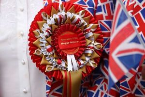 A rosette wishing Britain's Queen Elizabeth II a happy birthday pinned on a royal supporter outside Windsor Castle, on April 21, 2016.