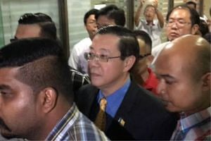 Penang Chief Minister Lim Guan Eng surrounded by Malaysian Anti-Corruption Commission officers walking out of his office in Komtar on June 29, 2016.