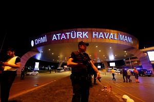 A riot police officer stands guard at the entrance of the Ataturk airport in Istanbul, Turkey.