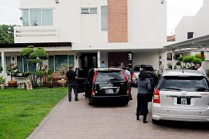 This photo taken in May shows Malaysian Anti-Corruption Commission officers in the driveway of Mr Lim Guan Eng's bungalow. He was arrested ahead of his arraignment in court today on allegations of corruption.