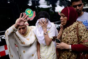 People react near the Holey Artisan restaurant after Islamist militants attacked the upscale cafe in Dhaka, Bangladesh, on July 2, 2016.