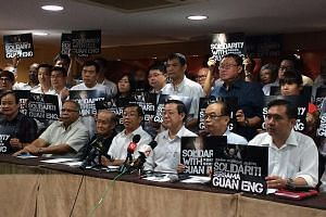 DAP leaders, together with secretary- general Lim Guan Eng (front row, third from right) were defiant at their leadership meeting yesterday, repeating their stand that the two corruption charges against Lim and a businesswoman were trumped up by the