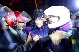 An injured member of the police personnel is carried away by his colleagues, after gunmen stormed a restaurant popular with expatriates in the diplomatic quarter of the Bangladeshi capital in Dhaka on July 1.