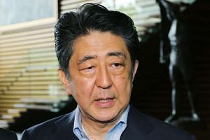 Japanese Prime Minister Shinzo Abe speaks to journalists after a Cabinet meeting on the siege.
