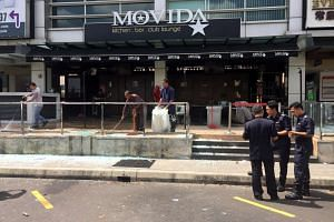 Police officers standing outside the Movida Bar following a grenade attack, in Puchong, near KL, on June 28, 2016.