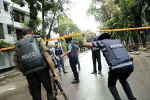 Policemen behind tape to restrict media and others near the Holey Artisan Bakery in Dhaka, Bangladesh on July 2.